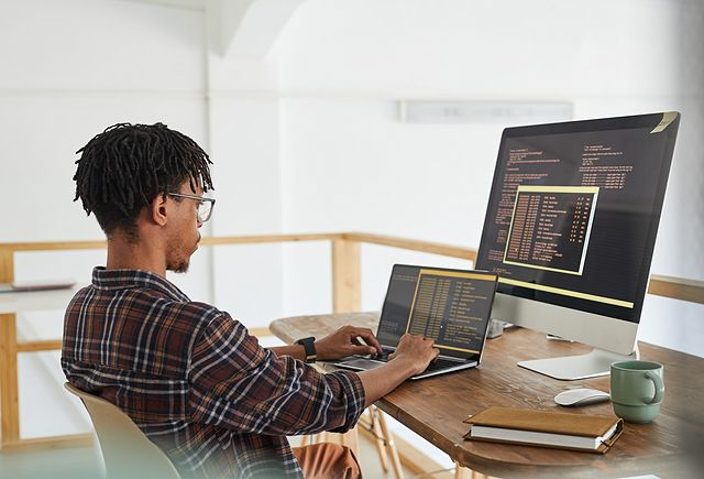 African-American IT developer typing on keyboard with black and orange programming code on computer screen and laptop in contemporary office interior