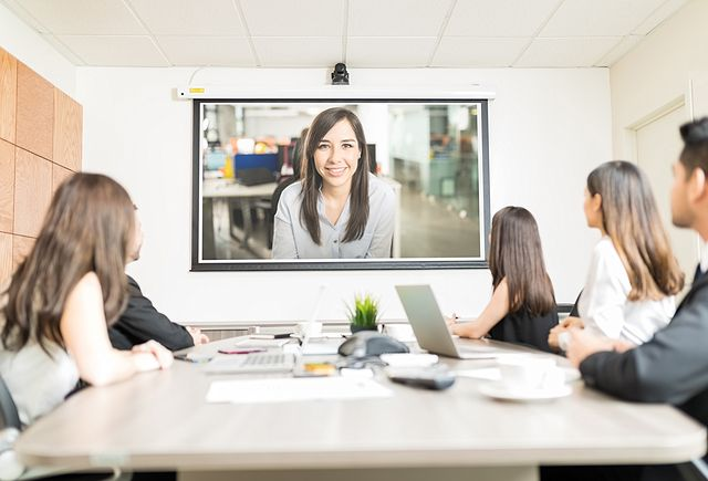 business people looking at blank projection screen while sitting at conference table