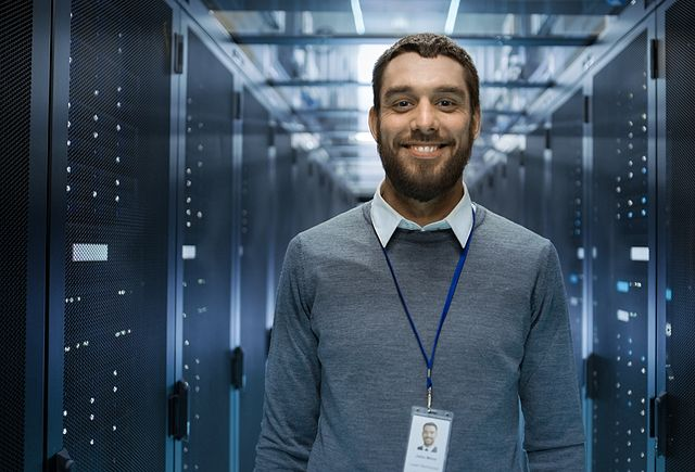 image of a smiling engineer standing in row of data servers