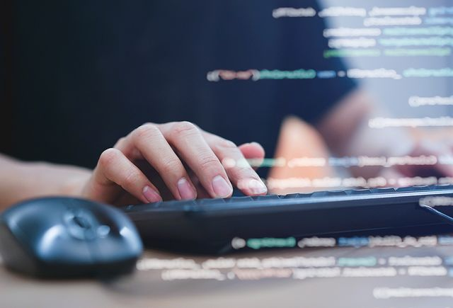 close up image of hands typing on external keyboard