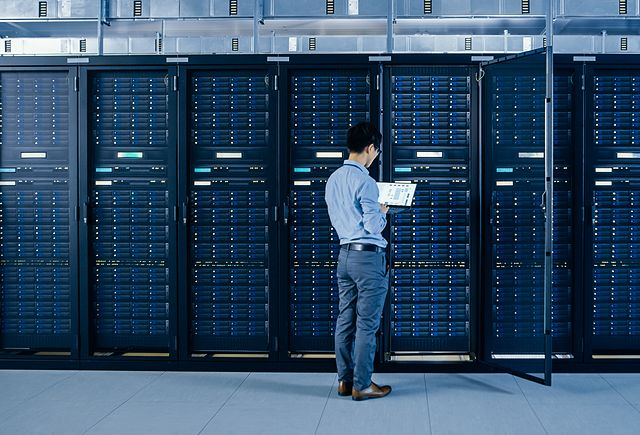 IT Engineer Standing Beside Open Server Rack Cabinets, Does Wireless Maintenance and Diagnostics Procedure with a Laptop.