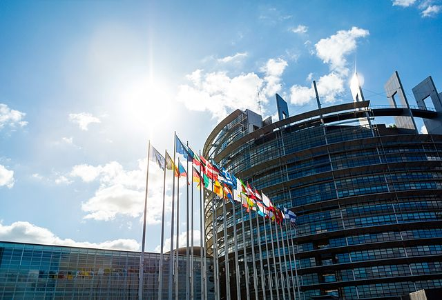 Wide angle view of large facade European PArliament building in Strasbourg with all EU member Flags including United Kingdom - clear blue sky and scattered clouds