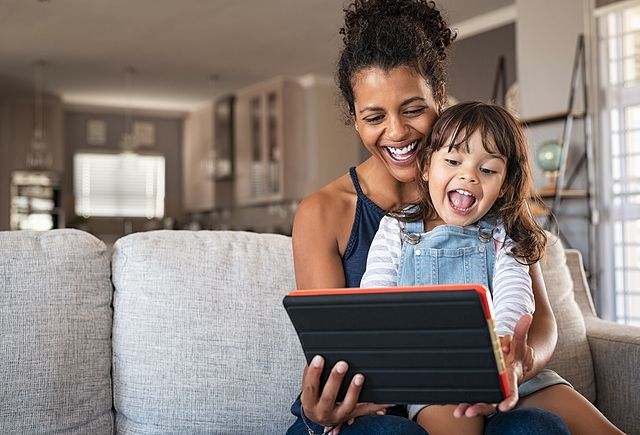 Young black mother and smiling daughter playing on digital tablet at home