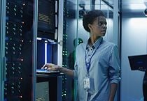 Portrait of African American woman working as IT engineer and standing among server racks in data center room