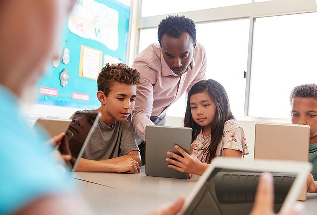 teacher showing kids how to use a tablet