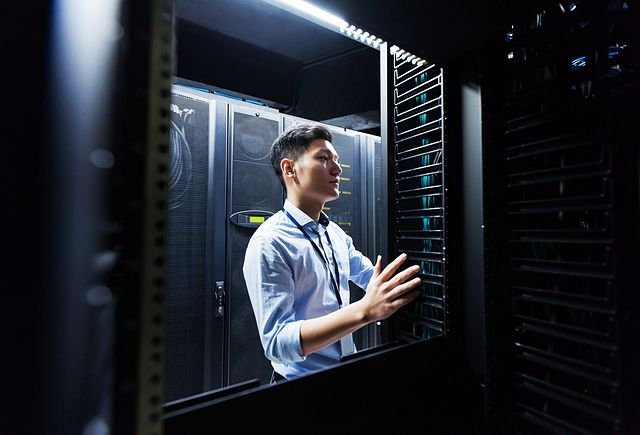 Young IT engineer inspecting data center servers.